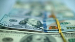 Hand in blue glove moving packs of US dollars on white surface. Close-up Stock Footage