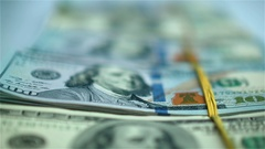 Hand in blue glove moving bundles of US dollars on white surface. Closeup Stock Footage
