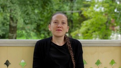 Portrait of a smiling girl with braid dressed in black sitting in the gazebo Stock Footage