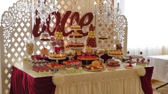 Candy bar, red colour, marsala. Table with wedding cake, sweets, candies Stock Footage