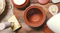 Slow motion milk being poured into an earthenware pot top view Stock Footage