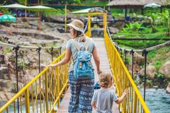 Mother and son are going on a suspension bridge. Traveling with children co.. Stock Photos