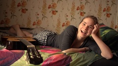Portrait of beautiful caucasian woman lying in bed and smiling with guitar Stock Footage