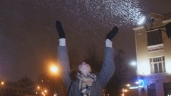 Young happy girl is enjoying the falling snow holding up his hands Stock Footage