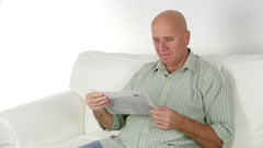 Businessman Very Disappointed Sitting Comfortable and Reading Newspaper. Stock Footage