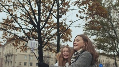 Two young girls friends do selfi autumn in one of the city streets Stock Footage
