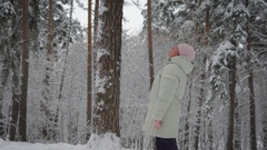 Elderly woman in warm clothing standing in the middle of snow-covered forest and Stock Footage