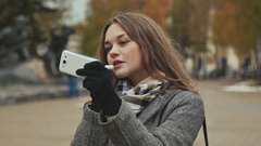 Young beautiful girl lipstick hygienic lipstick on a city street. Autumn. Cold Stock Footage