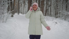 Kind woman, dressed in a bright pink hat and gloves, long white jacket with hood Stock Footage