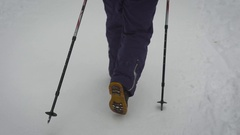 Close up of stepping legs of a woman in warm black trousers and heavy boots Stock Footage