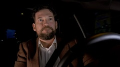 Handsome business man getting late for appointment stuck in traffic at night Stock Footage