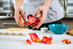 Woman throws about rose petals on table Stock Photos