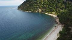Beautiful coast sandy beach aerial blue water horizon hilly trees bay coastline Stock Footage