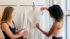 Female fashion designers measuring dress while working on a digital tablet Stock Footage