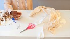 Female fashion designer preparing thread to stitch couture Stock Footage