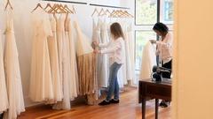 Female fashion designers arranging dress on clothes rail Stock Footage