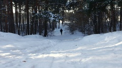 The man is running through a winter forest road Stock Footage
