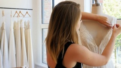 Female fashion designer adjusting the dress on mannequin Stock Footage