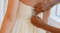 Woman trying on wedding dress with the assistance of fashion designer Stock Footage