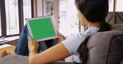 Millennial white girl chats on her tablet with greenscreen Stock Photos
