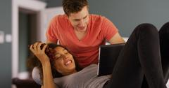 Portrait of mixed race couple looking at pictures on handheld tech device. Stock Photos