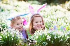 Kids on Easter egg hunt in blooming spring garden Stock Photos
