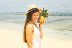 Girl in hat holding pineapple on the beach Stock Photos