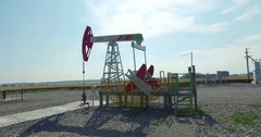 Oil pump jack, working oil pumps against sun - Aerial photography  Stock Footage