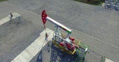 Aerial photography - Working oil pumps against sun / Oil pump jack Stock Footage