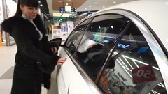 Woman inspecting her new car in showroom Arkistovideo