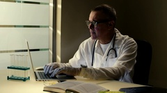 Professional elderly caucasian doctor in glasses wearing medical gown or uniform Stock Footage