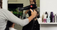 Female hairdresser blow drying her client hair Stock Footage
