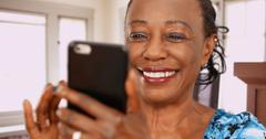 An elderly back woman swipes on her favorite dating app Stock Photos