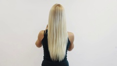 Blonde girl back playing with her long straighten hair in front of white wall Stock Footage