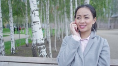 4K Portrait smiling businesswoman talking on cell phone in the park Stock Footage