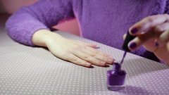 Young woman paints her nails with violet varnish Stock Footage