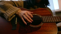 Young girl playing acoustic guitar at home Stock Footage