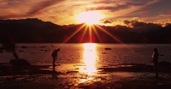 Male Skipping Rocks into Sunset at Lake Wanaka in New Zealand Stock Footage