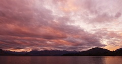 Sunset light behind clouds at Lake with Mounatins in BG Stock Footage