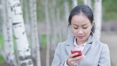 4K Portrait smiling Asian businesswoman looking at cell phone outdoors in park Stock Footage