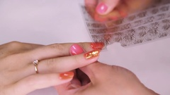 Female hand try roze floral pattern plastic sheet on painted nail orange polish Stock Footage
