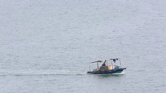 A small boat floats in the sea near the coast of the Cat Ba Island Stock Footage
