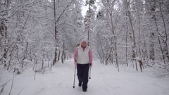 Stylishly dressed elderly woman is engaged in a new type of sports walking in Stock Footage