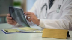 Male doctor looking at lungs x-ray, writing diagnosis, blank nameplate on table Stock Footage