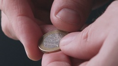 Poor man flipping one last euro coin between fingers Stock Footage