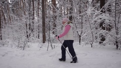 Elderly woman dressed in winter sport clothes quickly goes on the path using Stock Footage