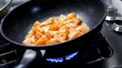Close up of a woman cooking tomato scrambled eggs in frying pan Stock Footage