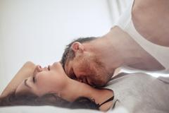 Young couple on bed enjoying romantic foreplay Stock Photos