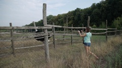 Beautiful girl makes video on the tablet ostrich at the farm. Steadycam shot. Stock Footage