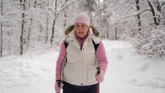 Elderly woman in a beautiful sports wear is engaged in Nordic walking on  snow Stock Footage